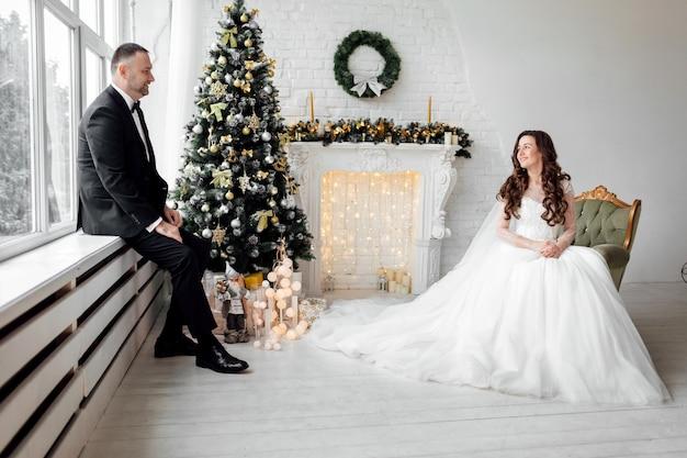 Jovem casal apaixonado noiva e noivo posando no estúdio em fundo decorado com árvore de natal no dia do casamento no natal. desfrute de um momento de felicidade e amor.
