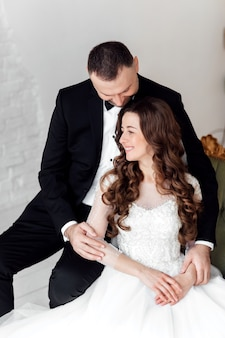 Jovem casal apaixonado noiva e noivo posando no estúdio em fundo decorado com árvore de natal no dia do casamento no natal.