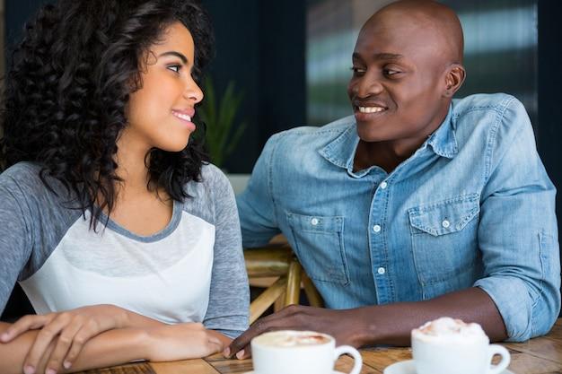 Jovem casal apaixonado olhando um para o outro à mesa de um café