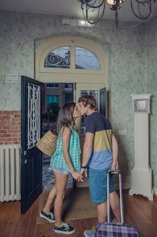 Jovem casal apaixonado por malas se beijando e partindo para o albergue depois de umas boas férias. férias e conceito de turismo.