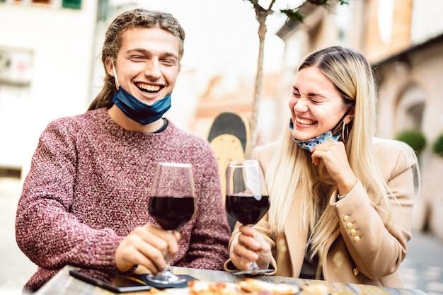 Jovem casal apaixonado por máscaras abertas se divertindo em um bar de vinhos ao ar livre