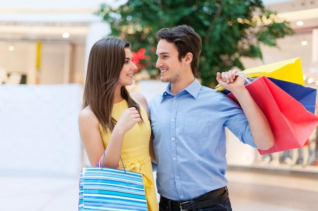 Jovem casal apaixonado por sacolas de compras
