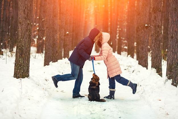 Jovem casal apaixonado por um cachorro andando no bosque nevado e se beijando