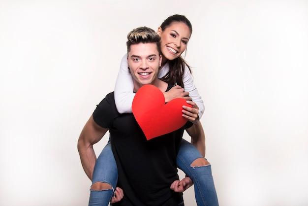 Jovem casal apaixonado por um grande coração vermelho isolado no fundo branco