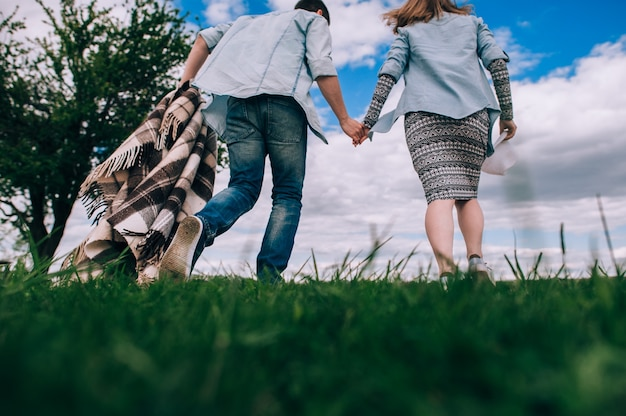 Jovem casal apaixonado por uma manta quadriculada correndo por um campo verde de mãos dadas. vista traseira e inferior. imagem matizada.