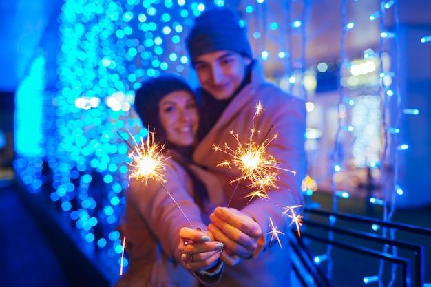 Jovem casal apaixonado queima de estrelinhas pela iluminação do feriado