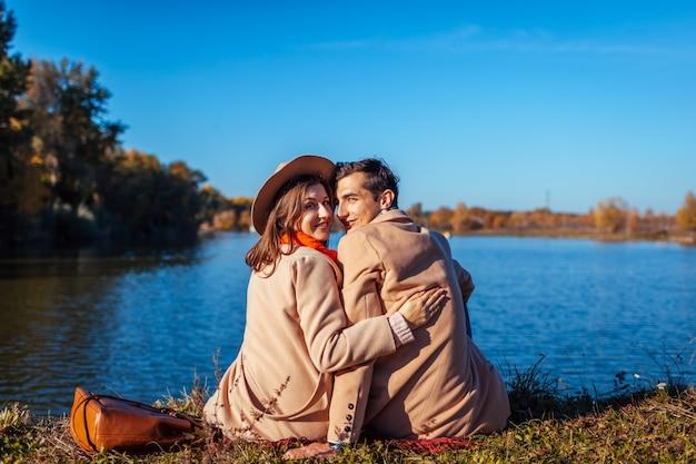 Jovem casal apaixonado, relaxando no lago de outono. homem e mulher felizes curtindo a natureza e abraçando