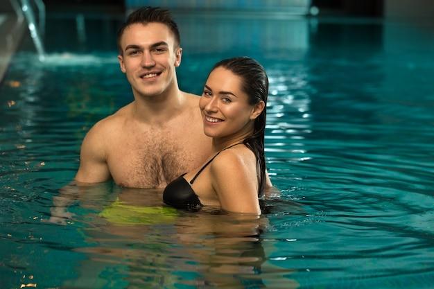 Jovem casal apaixonado relaxante na piscina spa juntos