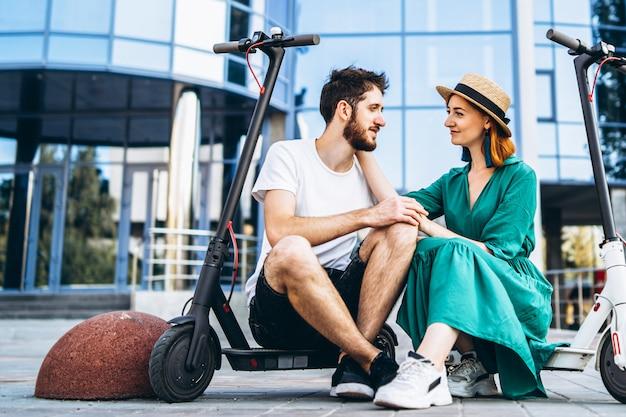Jovem casal apaixonado relaxante sentado perto de um edifício de vidro moderno com suas scooters elétricas. passeios na cidade grande