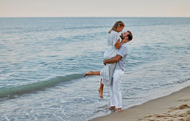 Jovem casal apaixonado romanticamente passa tempo na praia, curtindo um ao outro e férias à beira-mar.