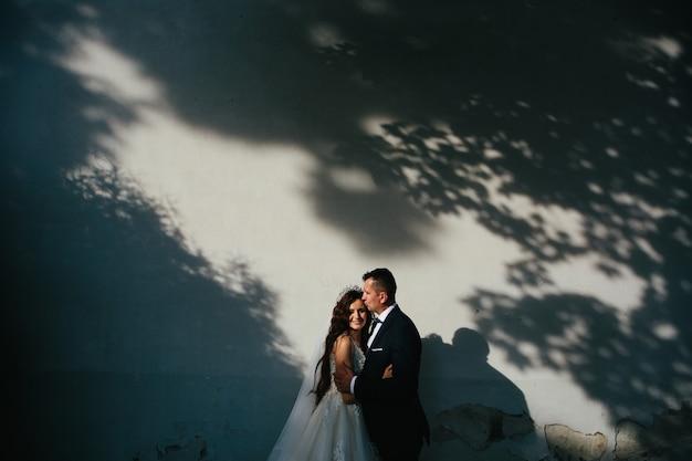 Jovem casal apaixonado se abraçando à sombra das árvores, pôr do sol, sessão de fotos de casamento