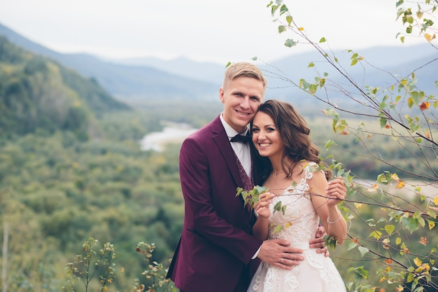 Jovem casal apaixonado se abraçando e sorrindo, foto de casamento, noiva e noivo