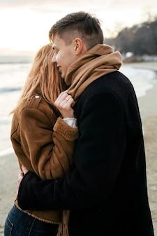 Jovem casal apaixonado se abraçando na praia no inverno
