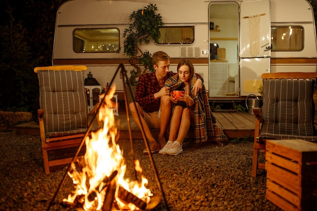Jovem casal apaixonado se abraçando perto da fogueira, fazendo um piquenique no acampamento na floresta