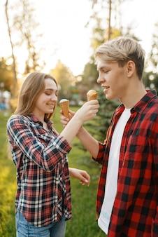 Jovem casal apaixonado se alimenta de sorvete no parque de verão.