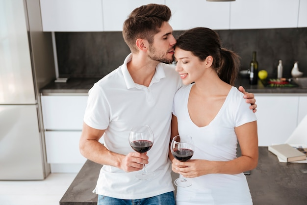 Jovem casal apaixonado se beijando e bebendo vinho tinto na cozinha