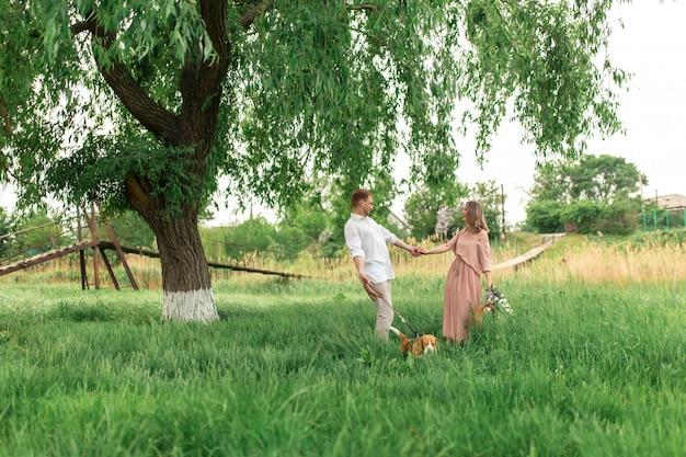 Jovem casal apaixonado se divertindo e correndo na grama verde no gramado com seu amado cão doméstico raça beagle e um buquê de flores silvestres