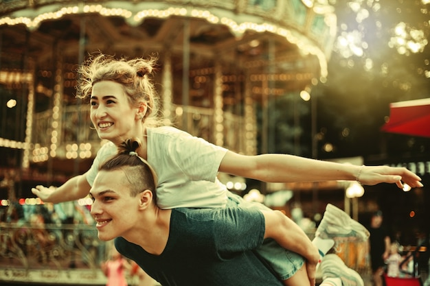 Jovem casal apaixonado se divertindo juntos no conceito de férias, amor e amizade do parque de diversões