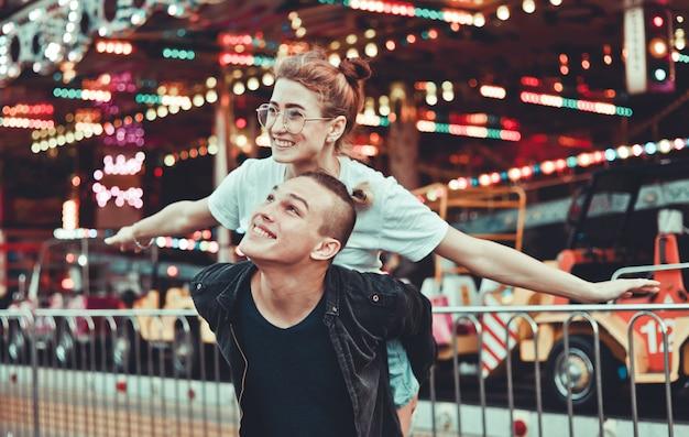 Jovem casal apaixonado se divertindo juntos no parque de diversões