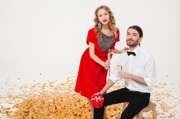 Jovem casal apaixonado, segurando copos e bebendo champanhe, comemorando o ano novo