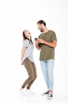 Jovem casal apaixonado segurando os telefones a rir.