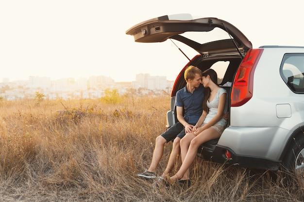 Jovem casal apaixonado, sentado em um carro com um porta-malas aberto