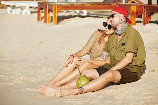 Jovem casal apaixonado sentado na praia