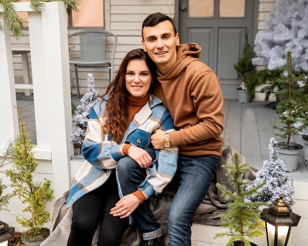 Jovem casal apaixonado, sentado na varanda. eles se abraçando e sorrindo.
