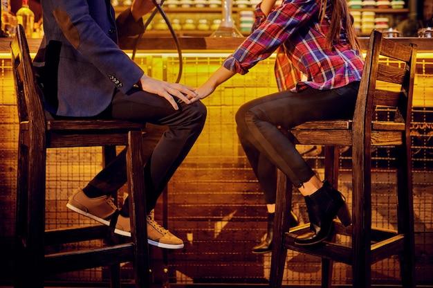 Jovem casal apaixonado sentado no balcão em um bar de narguilé, relaxando
