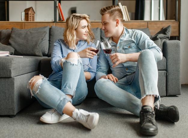 Jovem casal apaixonado sentado no chão no sofá e bebe vinho tinto, jantar romântico.