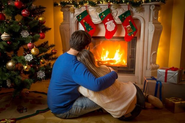 Jovem casal apaixonado, sentado no chão, olhando para a lareira acesa e a árvore de natal decorada