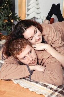 Jovem casal apaixonado sentado no chão perto da árvore de natal