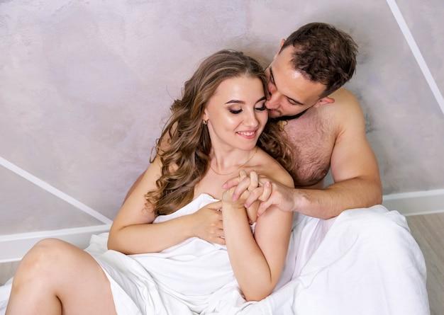 Jovem casal apaixonado, sentado no chão, se abraçando em lençóis brancos, clima romântico