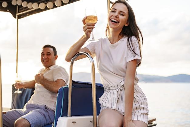 Jovem casal apaixonado, sentado no convés do iate, bebendo vinho