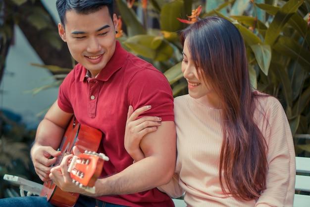 Jovem casal apaixonado, sentado no jardim, tocando violão e cantando.