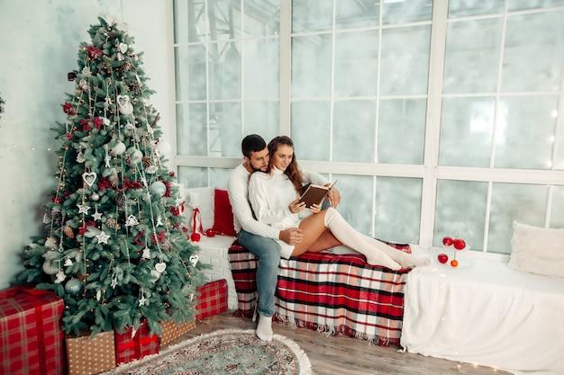 Jovem casal apaixonado sentado no parapeito da janela lendo um livro no interior da casa de natal