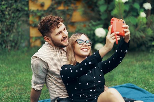 Jovem casal apaixonado tomando uma selfie com uma câmera instantânea