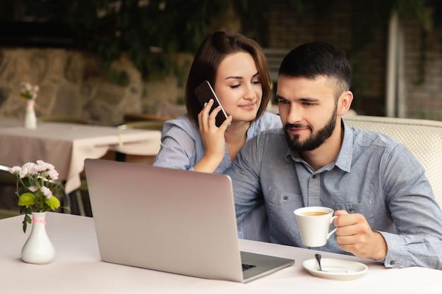 Jovem casal apaixonado, trabalhando em casa, homem e mulher sentada à mesa, trabalhando no laptop dentro de casa