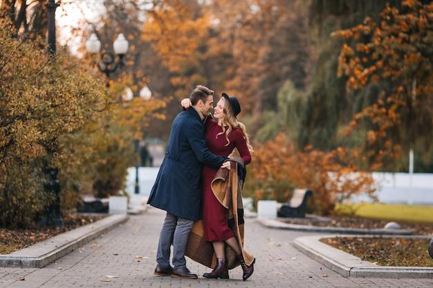 Jovem casal apaixonado, um homem bonito e uma mulher elegante em um vestido vermelho e um chapéu, se abraça e se divirta em um parque ...
