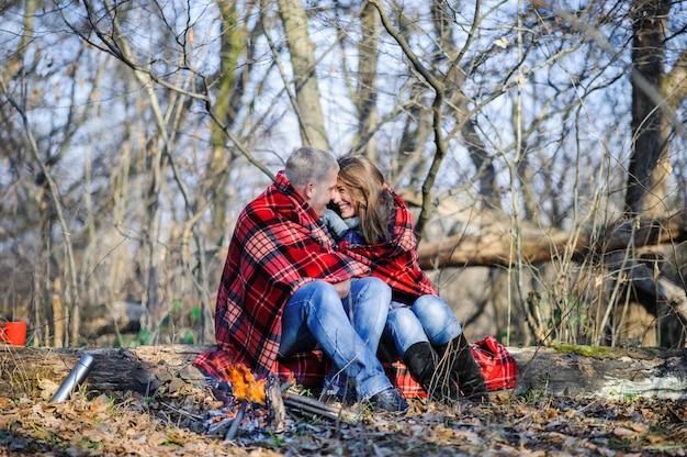 Jovem casal apaixonado, vestido de suéter azul, sentado com copos de café vermelho sobre a lenha na floresta de inverno