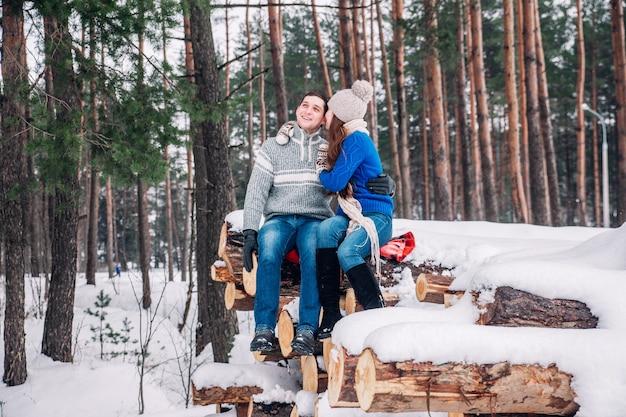Jovem casal apaixonado, vestido de suéter azul, sentado na lenha e abraçando na floresta de inverno