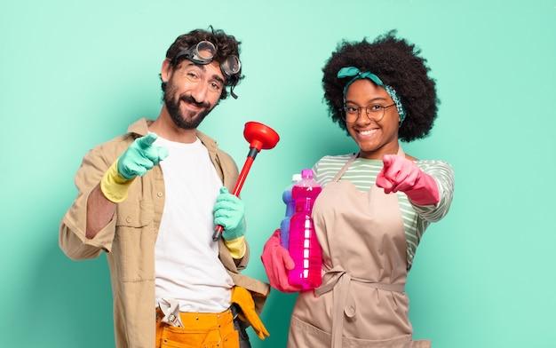 Jovem casal apontando para a câmera com um sorriso satisfeito, confiante e amigável, escolhendo você