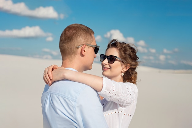 Jovem casal apreciando o pôr do sol nas dunas. viajante romântico caminha no deserto. conceito de estilo de vida de viagens de aventura