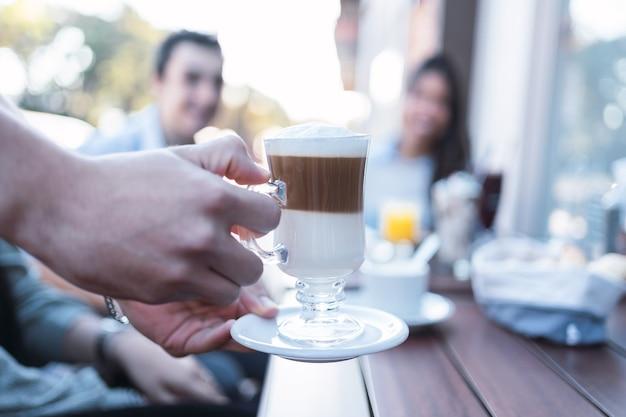 Jovem casal apreciando um cappuccino em um café.