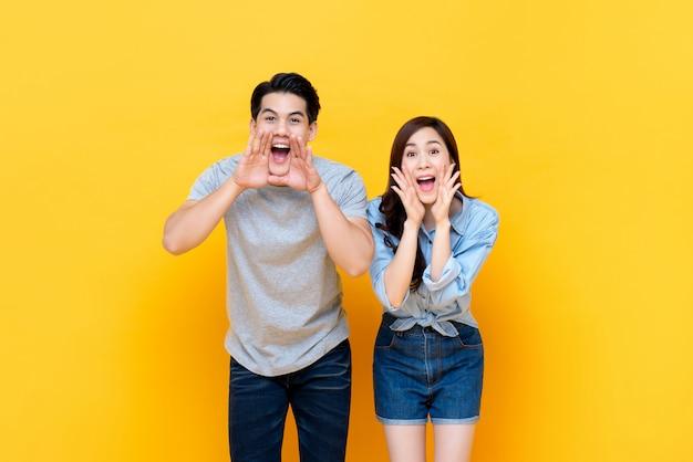 Jovem casal asiático adorável gritando com copo de mãos em volta da boca