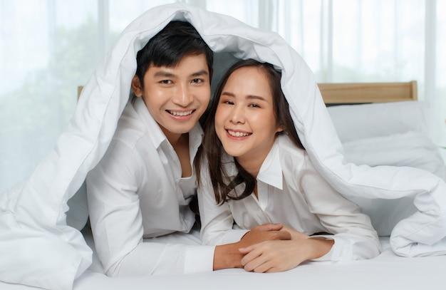 Jovem casal asiático atraente feliz deitado na cama juntos, olhando para a câmera com um cobertor cobrindo-os. fundo de cortina branca. conceito de amor e relacionamento feliz.