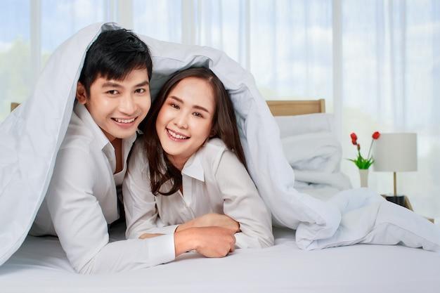 Jovem casal asiático atraente, feliz, deitado na cama, olhando para a câmera com um cobertor coberto