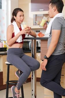 Jovem casal asiático bebendo deliciosos coquetéis de proteínas no bar da academia ou na academia