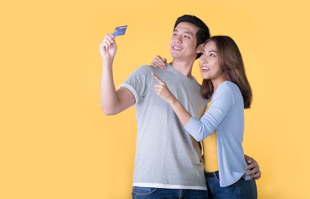 Jovem casal asiático com cartão de crédito isolado na parede amarela