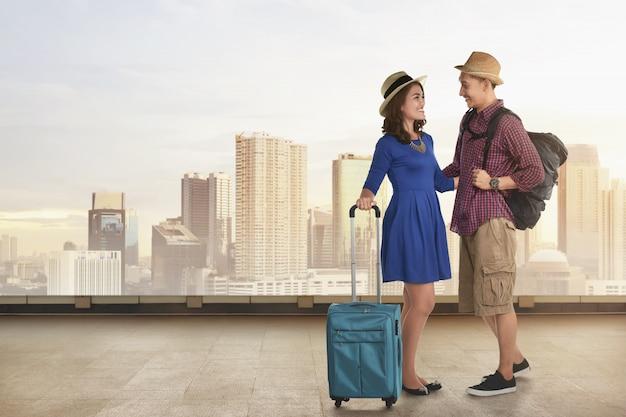 Jovem casal asiático com férias indo de mala